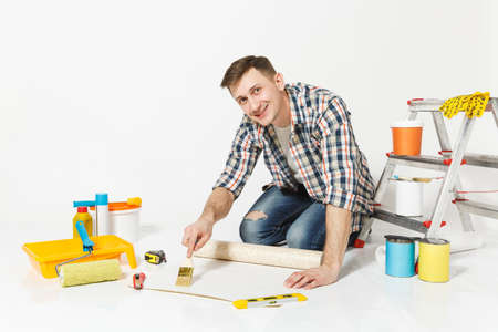 Young man sitting on floor with wallpaper roll, brush for gluing, instruments for renovation apartment room isolated on white background. Wallpaper painting accessories and tools. Repair home concept Reklamní fotografie