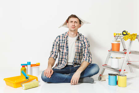 Male in newspaper hat with pencil behind ear sitting on floor with instruments for renovation apartment isolated on white background. Wallpaper, gluing accessories, painting tools. Repair concept