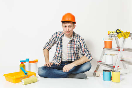 Skeptical man in orange protective helmet sitting on floor with instruments for renovation apartment isolated on white background. Wallpaper, gluing accessories, painting tools. Repair home concept Reklamní fotografie