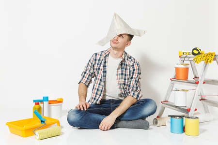 Confused tired man in newspaper hat falling on eye, sitting on floor with instruments for renovation apartment isolated on white background. Wallpaper gluing accessories, tools. Repair home concept