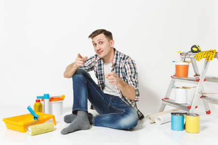 Smiling happy man in casual clothes sitting on floor with instruments for renovation apartment room isolated on white background. Wallpaper, gluing accessories, painting tools. Repair home concept Reklamní fotografie