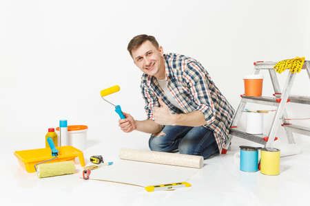 Young man sitting on floor with wallpaper roll, paint roller, instruments for renovation apartment room isolated on white background. Wallpaper gluing accessories, painting tools. Repair home concept