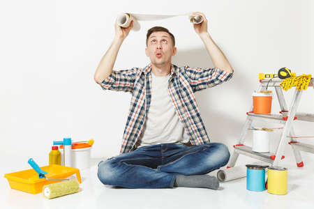 Confused perplexed man sitting on floor with roll of wallpaper above head, instruments for renovation apartment isolated on white background. Gluing accessories, painting tools. Repair home concept Reklamní fotografie