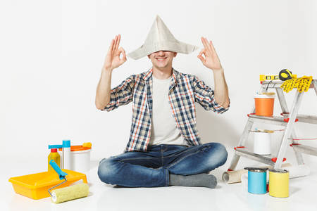 Happy man in newspaper hat sitting on floor meditating, doing yoga, relaxing with instruments for renovation apartment room isolated on white background. Wallpaper, gluing tools. Repair home concept