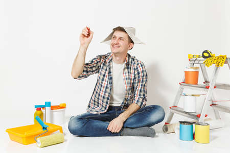 Fun man in newspaper hat writing pencil in air something on copy space. Instruments for renovation apartment isolated on white background. Wallpaper, gluing accessories painting tools. Repair concept Banco de Imagens