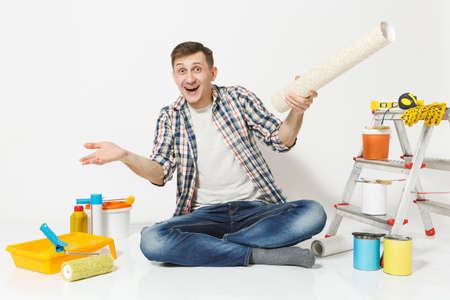 Smiling man spreading hands, sitting on floor with rolls of wallpaper, instruments for renovation apartment room isolated on white background. Gluing accessories, painting tools. Repair home concept