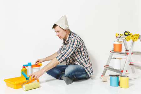Confused shocked man in newspaper hat spreading hands, sitting on floor with instruments for renovation apartment isolated on white background. Wallpaper gluing accessories tools. Repair home concept