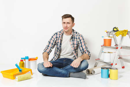 Serious pensive man in casual clothes sitting on floor with instruments for renovation apartment room isolated on white background. Wallpaper, gluing accessories, painting tools. Repair home concept