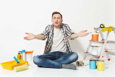 Confused shocked annoyed tired man spreading hands, sitting on floor with instruments for renovation apartment isolated on white background. Wallpaper, gluing accessories, tools. Repair home concept Reklamní fotografie