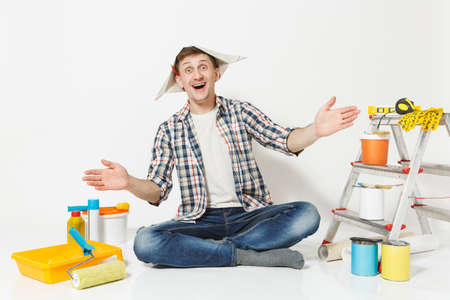 Fun man in newspaper hat with pencil behind ear sitting on floor with instruments for renovation apartment isolated on white background. Wallpaper, gluing accessories, painting tools. Repair concept