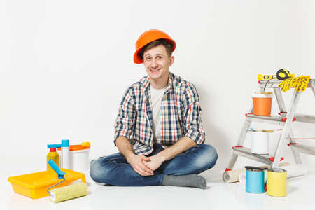 Smiling man in orange protective helmet sitting on floor with instruments for renovation apartment room isolated on white background. Wallpaper gluing accessories, painting tools. Repair home concept