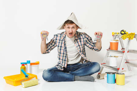 Fun crazy young man in newspaper hat with supermarket grocery push carts for shopping. Instruments for renovation apartment isolated on white background. Wallpaper painting tools. Repair home concept Stockfoto