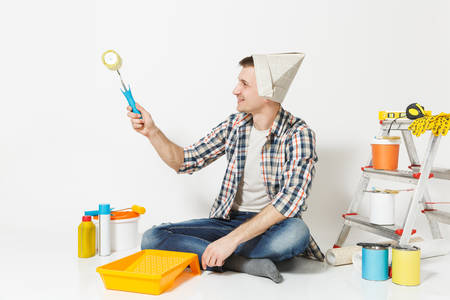 Man in newspaper hat sitting on floor, using paint roller, instruments for renovation apartment room isolated on white background. Wallpaper, gluing accessories, painting tools. Repair home concept Reklamní fotografie