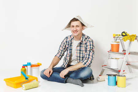 Fun happy smiling man in newspaper hat sitting on floor with instruments for renovation apartment room isolated on white background. Wallpaper, gluing accessories, painting tools. Repair home concept