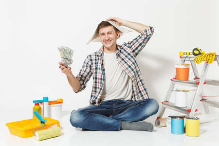 Happy man in newspaper hat holds bundle of dollars, cash money. Instruments for renovation apartment isolated on white background. Wallpaper, gluing accessories, painting tools. Repair home concept