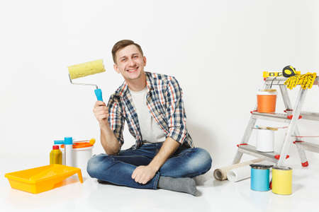 Man in casual clothes sitting on floor with paint roller, instruments for renovation apartment room isolated on white background. Wallpaper, gluing accessories, painting tools. Repair home concept