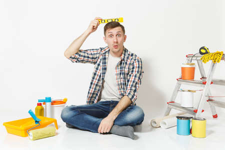 Fun happy male sitting on floor with bubble spirit level on head, instruments for renovation apartment isolated on white background. Wallpaper, gluing accessories, painting tools. Repair home concept