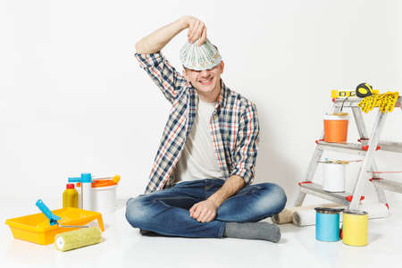 Young man holds bundle of dollars, cash money, sits on floor with instruments for renovation apartment isolated on white background. Wallpaper, gluing accessories, painting tools. Repair home concept