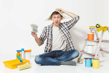 Shocked man in newspaper hat holds bundle of dollars, cash money. Instruments for renovation apartment isolated on white background. Wallpaper, gluing accessories, painting tools. Repair home concept