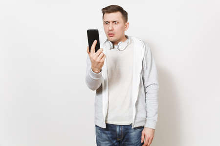 Young handsome student in t-shirt and light sweatshirt with headphones around neck takes his frustrated face on mobile phone in studio on white background. Concept of communication. Stock Photo