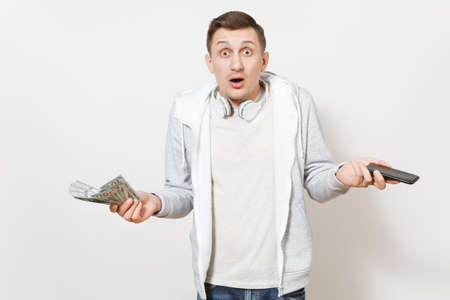 Young handsome student in t-shirt and light sweatshirt with headphones around neck holds dollar bills and mobile phone in hands in perplexity in studio on white background. Concept of success.