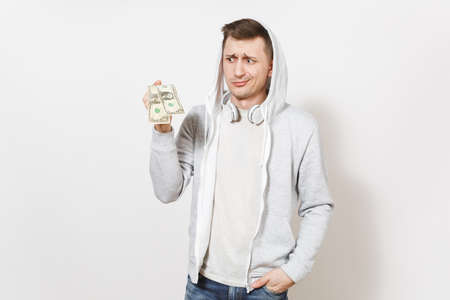 Young handsome student in t-shirt, blue jeans and light sweatshirt with hood with headphones holds two one-dollar bills and perplexedly looks in studio on white background. Concept of emotions.