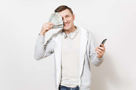 Young handsome smiling student in t-shirt and light sweatshirt with headphones around neck cover face with dollar bills and hold mobile phone in hand in studio on white background. Concept of success. Stok Fotoğraf