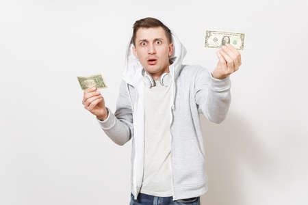 Young handsome student in t-shirt and light sweatshirt with hood with headphones holds one-dollar bills and surprised shows them in studio on white background. Concept of emotions.