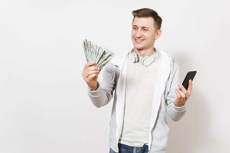 Young handsome smiling student in t-shirt and light sweatshirt with headphones around neck holds dollar bills and mobile phone in hands in studio on white background. Concept of success.