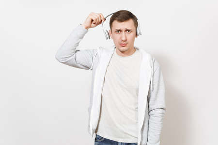Young handsome student in t-shirt and light sweatshirt listening to music with white wireless headphones and in perplexity removes them in studio on white background. Concept of emotions.