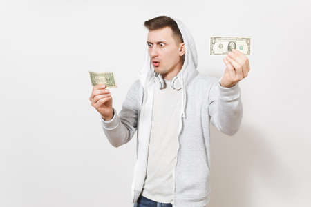 Young handsome student in t-shirt and light sweatshirt with hood with headphones holds one-dollar bills and surprised looks at them in studio on white background. Concept of emotions.