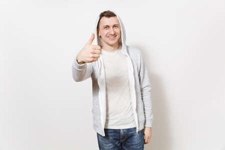 Young handsome smiling man in t-shirt, blue jeans and light sweatshirt shows gesture thumbs up and rejoices isolated on white background. Concept of emotions, good mood. Copy space for advertisement