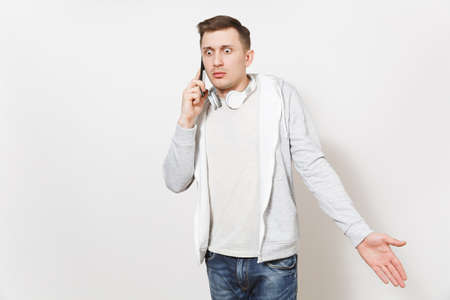 Young handsome student in t-shirt and light sweatshirt with headphones around neck talks on mobile phone and looks confused in studio on white background. Concept of communication.