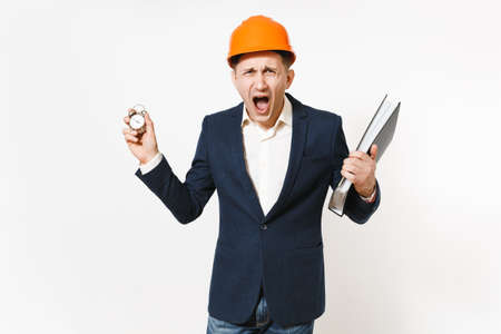Irritated dissatisfied businessman in dark suit, protective construction helmet screaming and holding folder for papers document and alarm clock isolated on white background. Time is running out Stock fotó