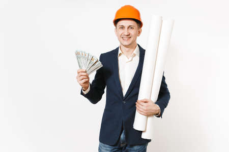 Young concerned businessman in dark suit, protective hardhat holding bundle of dollars, cash money and clinging to face isolated on white background. Male worker for advertisement. Business concept Stock fotó