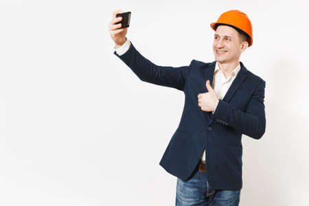 Young handsome smiling businessman in dark suit, protective hardhat showing thumb up and doing selfie on mobile phone isolated on white background. Male worker for advertisement. Business concept Stock fotó