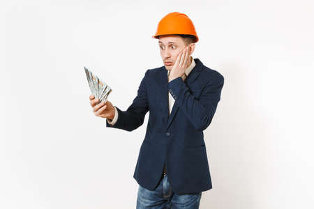 Young concerned businessman in dark suit, protective hardhat holding bundle of dollars, cash money and spreading hands isolated on white background. Male worker for advertisement. Business concept