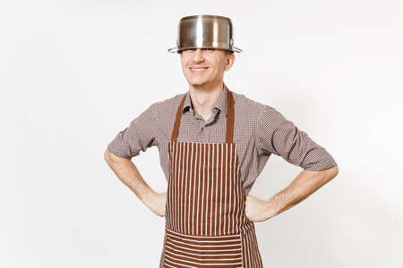 Fun man in striped apron with silver stainless glossy aluminium empty stewpan, pan or pot on head isolated on white background. Male housekeeper or houseworker. Kitchenware, dishes, cuisine concept