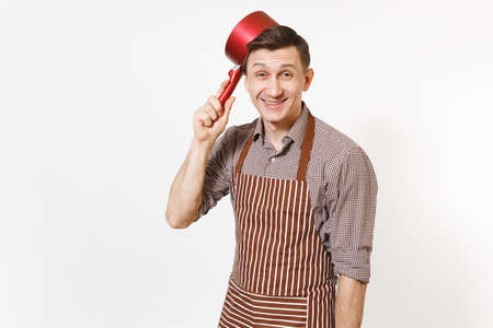 Young fun crazy happy man chef or waiter in striped brown apron, shirt holding red empty stewpan on head isolated on white background. Male housekeeper or houseworker. Kitchenware and cuisine concept