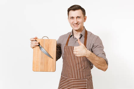 Young smiling man chef or waiter in striped brown apron, shirt holding wooden cutting board, knife isolated on white background. Male housekeeper or houseworker. Domestic worker for advertisement