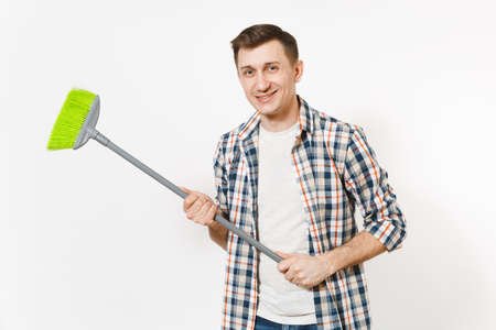 Young smiling happy housekeeper man in checkered shirt holding and sweeping with green broom isolated on white background. Male doing house chores. Copy space for advertisement. Cleanliness concept