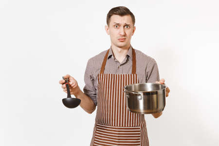Man chef in striped brown apron holding silver stainless glossy aluminium empty stewpan, pan or pot, ladle isolated on white background. Male housekeeper or houseworker. Kitchenware, dishes concept