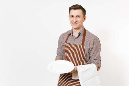 Young man chef or waiter in striped brown apron, shirt holding white round empty clear plate, towel napkin isolated on white background. Male housekeeper or houseworker. Domestic worker, copy space