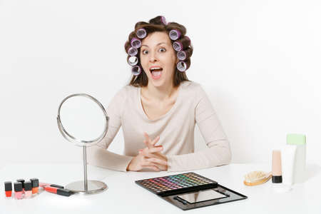 Fun young woman with curlers on hair sitting at table applying makeup with set facial decorative cosmetics isolated on white background. Beauty female fashion lifestyle concept. Area with copy space