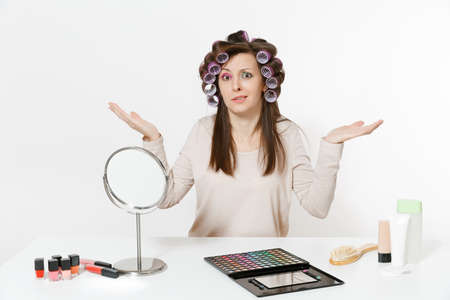 Irritated woman with curlers spreading hands, sitting at table applying makeup with set facial decorative cosmetics isolated on white background. Beauty female fashion lifestyle concept. Copy space