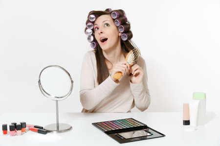 Fun woman with curlers using combing with comb her hair, sitting at table applying makeup with set facial decorative cosmetics isolated on white background. Beauty female fashion lifestyle concept