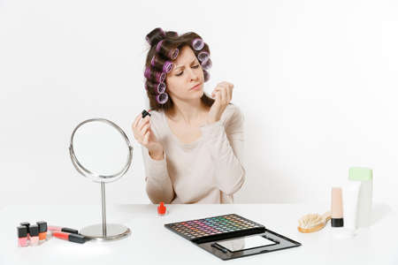 Fun woman with curlers painting nails with red nail polish, sitting at table applying makeup with set facial decorative cosmetics isolated on white background. Beauty female fashion lifestyle concept Фото со стока