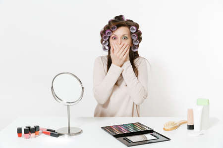 Fun woman with curlers cover mouth with hands, sitting at table applying makeup with set facial decorative cosmetics isolated on white background. Beauty female fashion lifestyle concept. Copy space