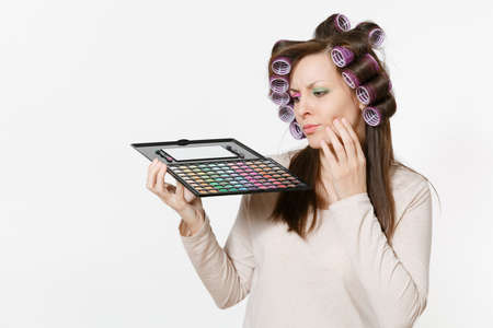 Fun young woman with curlers on hair with palette colorful eyeshadows isolated on white background. Makeup with set facial decorative cosmetics. Beauty fashion lifestyle concept. Area with copy space