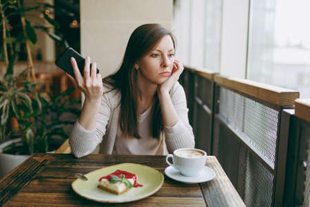 Young woman sitting alone in coffee shop at table with cup of cappuccino, cake, relaxing in restaurant during free time. Young female talking on mobile phone, having rest in cafe. Lifestyle concept 免版税图像
